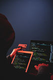 Cybercrime Scam. Back view of hooded internet criminal hacking database on laptop in the dark Stock Photo