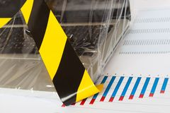 Laptop secured by Police - yellow tape and foil closeup Stock Photo