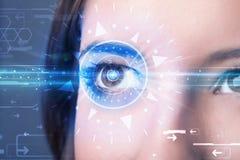 Cybermeisje die met technolgy oog blauwe iris onderzoeken stock fotografie