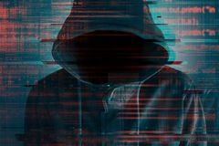 Cybersecurity, computer hacker with hoodie. And obscured face, computer code overlaying image stock image