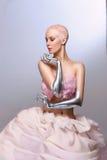 Cybervrouw van de toekomst met kleikapsel, zilveren handen en rok stock fotografie