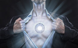 Cyborg artificial being opens shirt. Cyborg rips off his shirt showing up beating light plasma heart Stock Images