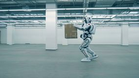 Droid works, carrying a box, side view. A cyborg carries one box in hands stock video footage
