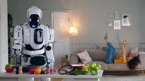 Cyborg et concept humain Le droid blanc fait cuire tandis qu'une femme a l'amusement avec un smartphone banque de vidéos