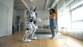 Cyborg et concept humain Une femme touche le droid blanc, se tenant dans une chambre clips vidéos