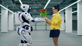 Cyborg gifts tulips to a smiling young woman, standing in a room. stock video