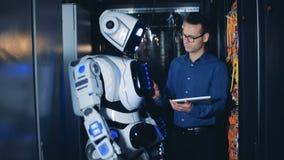 Cyborg hebt seine Hand unter Steuerung eines männlichen Ingenieurs an stock video