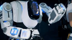 Cyborg herhaalt bewegingen na een jonge mens in virtuele werkelijkheidshoofdtelefoon stock footage