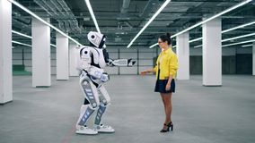 Cyborg holds girl`s hand while she smiles at it. stock video