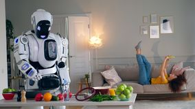 Cyborg and human concept. Droid cooks dinner while a girl having fun. Droid cooks dinner while a girl having fun. 4K stock footage