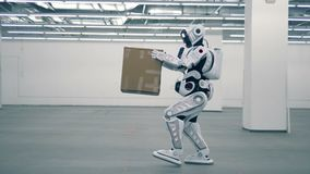 Cyborg is lifting a carton box and carrying it. 4K stock footage