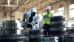 Cyborg przenosi metal części pod pracownika nadzorem zdjęcie wideo