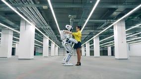 Cyborg spotykający i młoda kobieta ściskamy each inny podczas gdy zbiory