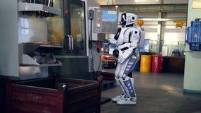 Cyborg werkt bij een fabriek die, die machines controleert en op een tablet typt stock videobeelden