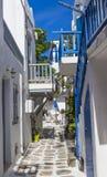?? ?? cyclades Mykonos?? 在传统狭窄的街道上的一个庭院有蓝色门的、窗口和阳台和白色 免版税库存图片
