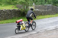 Cycle camping vacation. Man riding his mountain bike with his camping trailer behind completewith bed roll stock photo