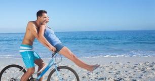 Cycle insouciant d'équitation de couples à la plage Images stock