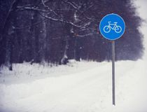 Cycle lane sign covered with snow against a dark forest Royalty Free Stock Images