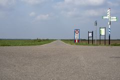 Cycle paths, bicycle lanes in the polder of the flat landscape of the Netherlands at the horizon a blue sky with white clouds. Bicycle lanes and many signs in stock photos