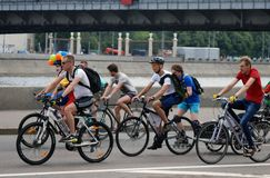 Cycle race in Moscow. Men on bikes. Many people ride bikes. They participate in a cycle race in Moscow city center on June 16, 2013 in Moscow. The Moscow river Royalty Free Stock Image