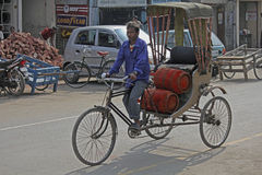 Cycle rickshaw. Man carrying LPG gas cylinders in a cycle rickshaw. dibrugarh assam, india Royalty Free Stock Image