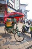 Cycle Rickshaw in a busy street, Zhujiajiao, China. Cycle Rickshaw in a busy street, with a red canopy & traditional buildings behind, Zhujiajiao, China royalty free stock image