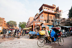 Cycle rickshaw drive through the busy asian street full of pedestrians Royalty Free Stock Image