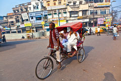 Cycle rickshaw driver with passenger in Chawri Bazar, Delhi earl Royalty Free Stock Image