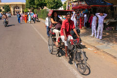 Cycle rickshaw driving in the streets of Jaipur, Rajasthan, India Royalty Free Stock Photo