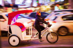 Cycle rickshaw in motion blur on the Champs Elysees in Paris, France. Paris, France - October 19, 2016: cycle rickshaw in motion blur on the Champs Elysees with royalty free stock photography