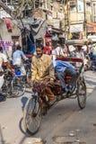 Cycle rickshaw with passengers. DELHI, INDIA - NOVEMBER 11, 2011: Cycle rickshaw with passenger in the streets in Delhi, India. Cycle rickshaws were introduced stock photo