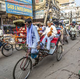 Cycle rickshaws with passengers in the streets of Delhi. DELHI, INDIA - NOVEMBER 11, 2011: Cycle rickshaws with passenger in the streets in Delhi, India. Cycle royalty free stock image