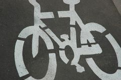 Cycle Road Symbol. Close-up of white painted symbol of a cycle. It is situated on the tarmac in a bike lane Stock Image