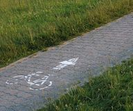 Cycle route from paving stones and grass Royalty Free Stock Images