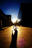 Cycle Shadow. Photograph of a youth riding his bike in front of a UK shopping center Royalty Free Stock Photos