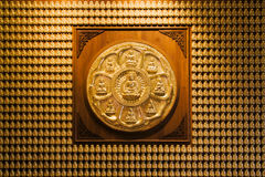 Cycle sign of nine golden buddha. And many golden buddha image on wood wall Stock Photography