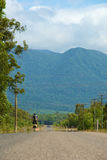 Cycle to the hills. Road leading to mountain range with person on bicycle riding there Stock Photo