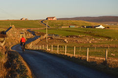 Cycle touring on Shetland Islands. Man cycle touring on the road of Shetland Islands stock photo