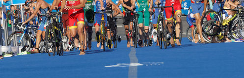 Cycle wheels, running feet of colorful triathletes Stock Photos