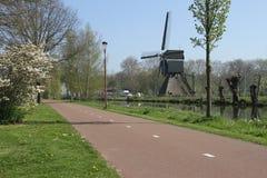 Cyclepath abandonné avec les fleurs et le moulin à vent images stock