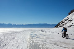 Cycler on the ice of Baikal lake. A cycler is riding on the ice of Baikal lake Stock Photos