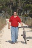 Cycler op de kust die met fiets loopt Stock Afbeeldingen