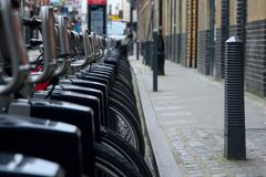Cycles. Transport for London. Docking station. Santander Cycles lined up at a docking station in central London. Santander Cycles is a public bicycle hire scheme royalty free stock images