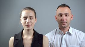 Cyclical video of man and woman on grey background. Video of man and woman sitting near on grey background stock video footage