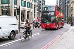 Cyclicts y autobús rojo moderno de Londres Fotografía de archivo