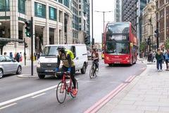 Cyclicts y autobús rojo moderno de Londres Fotos de archivo libres de regalías