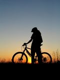 Cycling. Mountain biker girl silhouette in sunrise Royalty Free Stock Images