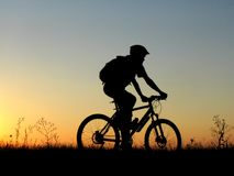 Cycling. Mountain biker girl silhouette in sunrise stock photo