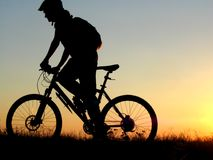Cycling. Mountain biker girl silhouette in sunrise stock image
