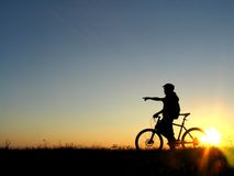Cycling. Mountain biker girl silhouette in sunrise royalty free stock image